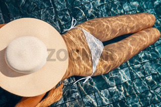 Unrecognizable woman in big hat with sexy slim body relaxing on the swimming pool