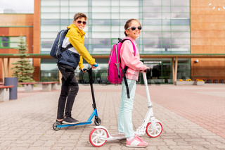 school children with backpacks riding scooters