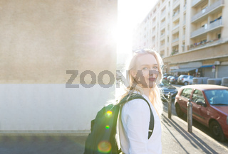 Portrait of woman with backpack on the street on sunset time.