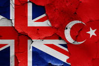 flags of UK and Turkey painted on cracked wall