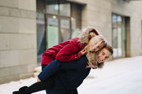 Young handsome guy giving girlfirend piggyback ride