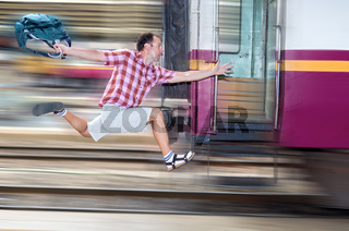 Tourist with bag running behind the train. A man runs for a moving wagon. Backpacker hurries for train departing from the station. Journey to the last minute.