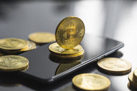 Golden bitcoin coin on a smartphone with a lot of bitcoins coins on a table. Virtual cryptocurrency concept. Mining of bitcoins online bussiness. Bitcoins trading.