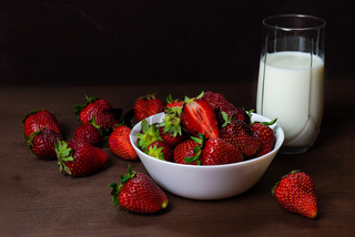Fresh strawberries in ceramic bowl and a glass of milk  on dark wooden background. Selective focus. - Image