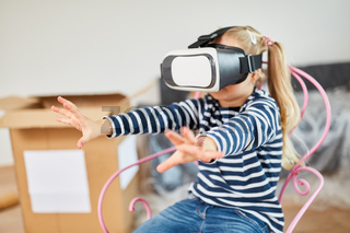 Mädchen mit VR Brille spielt im neuen Haus