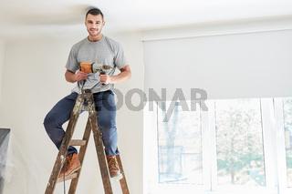 Junger Mann als Heimwerker mit Bohrmaschine
