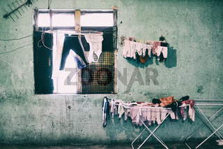 Children clothes hanged to dry near an eroded window in a decayed building with green walls.