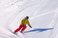 Young woman downhill skiing on an open slope at a ski resort in the Canadian Rocky Mountains, Alberta