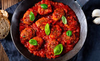 Baked mini meatballs in tomato sauce with basil