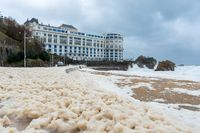 Foam on the Grande Plage beach and its quay, France
