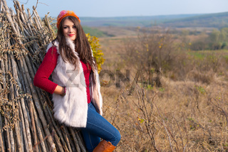 Beautiful girl smiling at the camera, in stylish fashion clothes in autumn scenery outdoors. Gorgeous romantic young woman in the countryside on a hill, in a sunny day