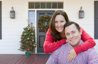 Happy Young Couple On Front Porch of House With Christmas Decorations
