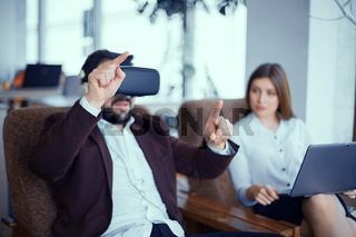 Adult bearded man with virtual reality vr glasses with woman at office