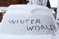 winterworld Schriftzug auf verschneiter Autoscheibe