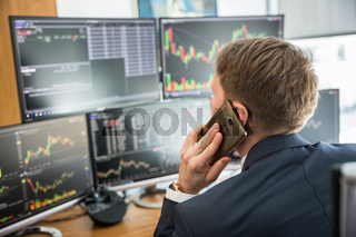 Over the shoulder view of stock broker trading online, talking on mobile phone.
