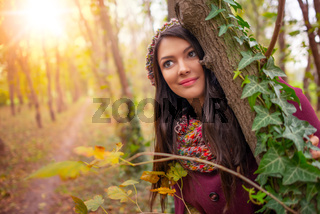 Close-up portrait of a gorgeous romantic young woman with beautiful long brown hair, in nice warm autumn sunlight, looking away from the camera. Shot in natural light, retouched, vibrant colors
