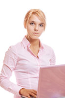 Beautiful young blonde woman working on a pink laptop