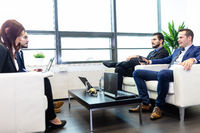 Business people sitting at working meeting in modern corporate office.