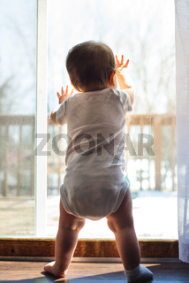 baby crawling up the window to stand