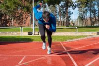 Young Man Starting sprint on Running Track.