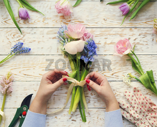 Florist at work. Woman making bouquet of spring flowers