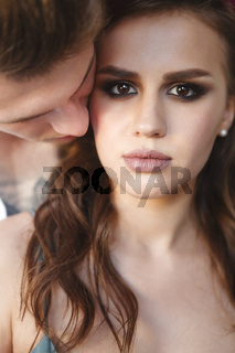 Tattoed stylish guy hugging his beautiful girlfriend