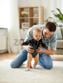 father helping baby daughter with walking at home