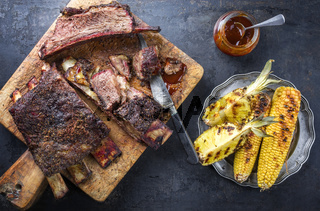 Barbecue sliced chuck beef ribs with hot rub with pineapple and corn as top view sliced on a wooden cutting board