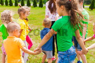 Children holding hands and standing in circle