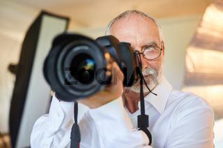 Professioneller älterer Fotograf als Porträtfotograf