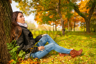 Beautiful romantic girl in a park autumn scenery, sitting down and leaning against a tree, enjoying the perfect weather in a sunny day. Gorgeous young woman outdoors. Full length body shot
