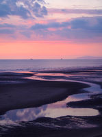 twilight view of a dark beach with a pink sky after sunset with blue clouds reflected in the water at low tide and a calm sea in blackpool lancashire