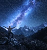 Man with raised up arms on the stone and Milky Way