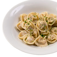 Portion of pelmeni with greenery on white plate