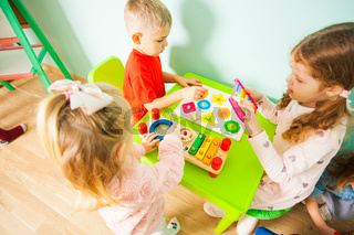 Toddler boy and girls sitting at the table in playroom.