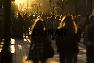 Two young women walking in crowd on the pedestrian street at summer sunset