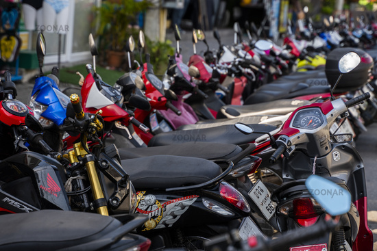 KRABI, THAILAND - JULY 10, 2019. Usual crowded parking place in Krabi with full of motorbikes. A lot of motorcycles parking in rows at sidewalk in tourustic place.