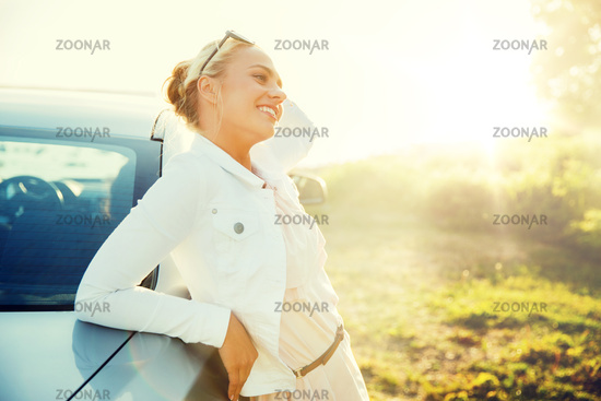 happy teenage girl or young woman near car