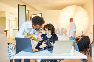 Fotoassistent mit Checkliste und Fotografin