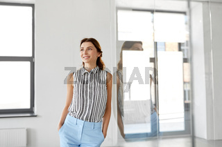 smiling businesswoman at office glass wall