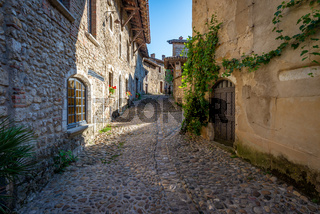 Tourist walking on a cobblestone street of Perouges, France