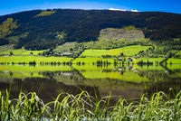 A majestic rural panorama view of green farmland, trees, quiet lake and mountains in the countryside, nature summer scenery with sunlight in a perfect place for meditation, zen and recreation