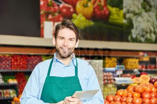 Lächelnder Mann als Verkäufer im Supermarkt