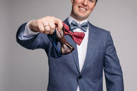 Smiling man insmart suit keeping bow ties in hand