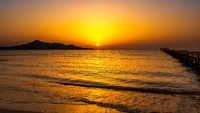 Solar disc in sunrise with silhouette of mountains and pier, panorama, Mallorca, Spain