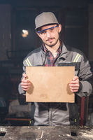 Portrait of a young carpenter in overalls and goggles with a mock up board holding a blank sign in his hands in his home workshop