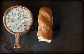 A bowl of Clam Chowder  and a baguette on a baking sheet
