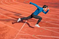 Runner starting his sprint on running track in a stadium.