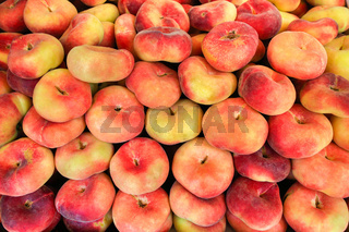 Many colorful fresh forest peaches at market