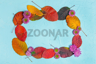 Frame of autumn leaves and flowers.